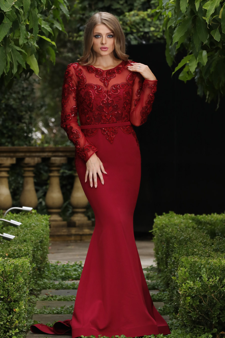Full length fit and flare gown, with a lace bodice, full length sleeve. The skirt is plain with a detailed train. Shown in the colour Burgundy.