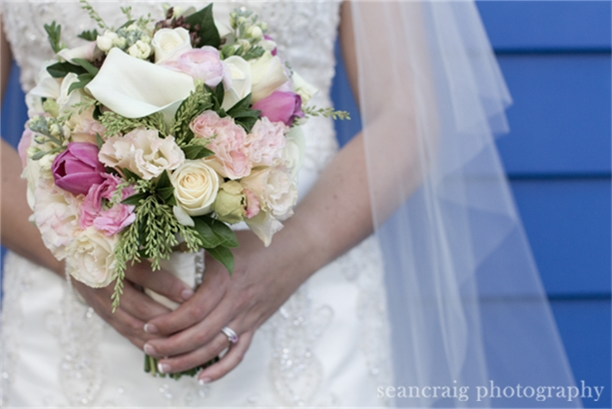 Mid shot of bride holding flowers with two hands