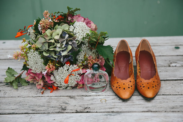 Wedding bouquet placed on table next to bottle and shoes