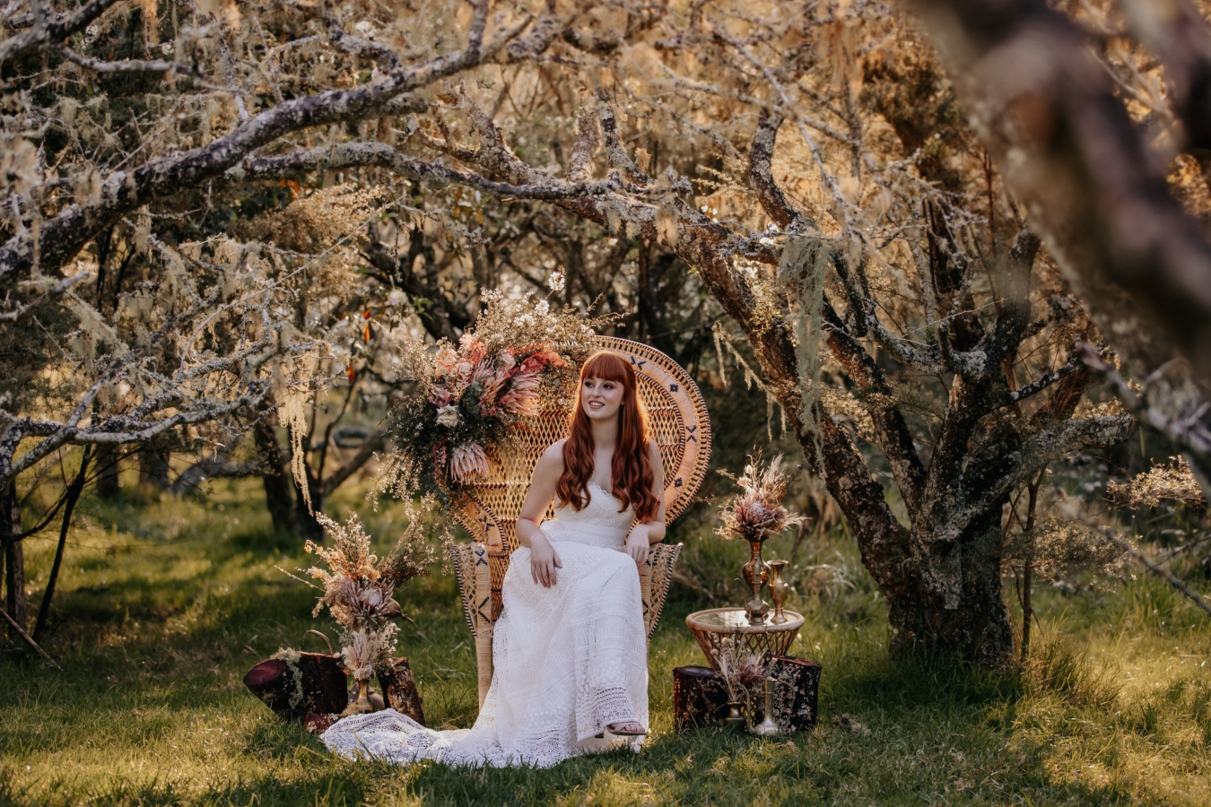 Bride on cane chair in middle of orchard amongst trees