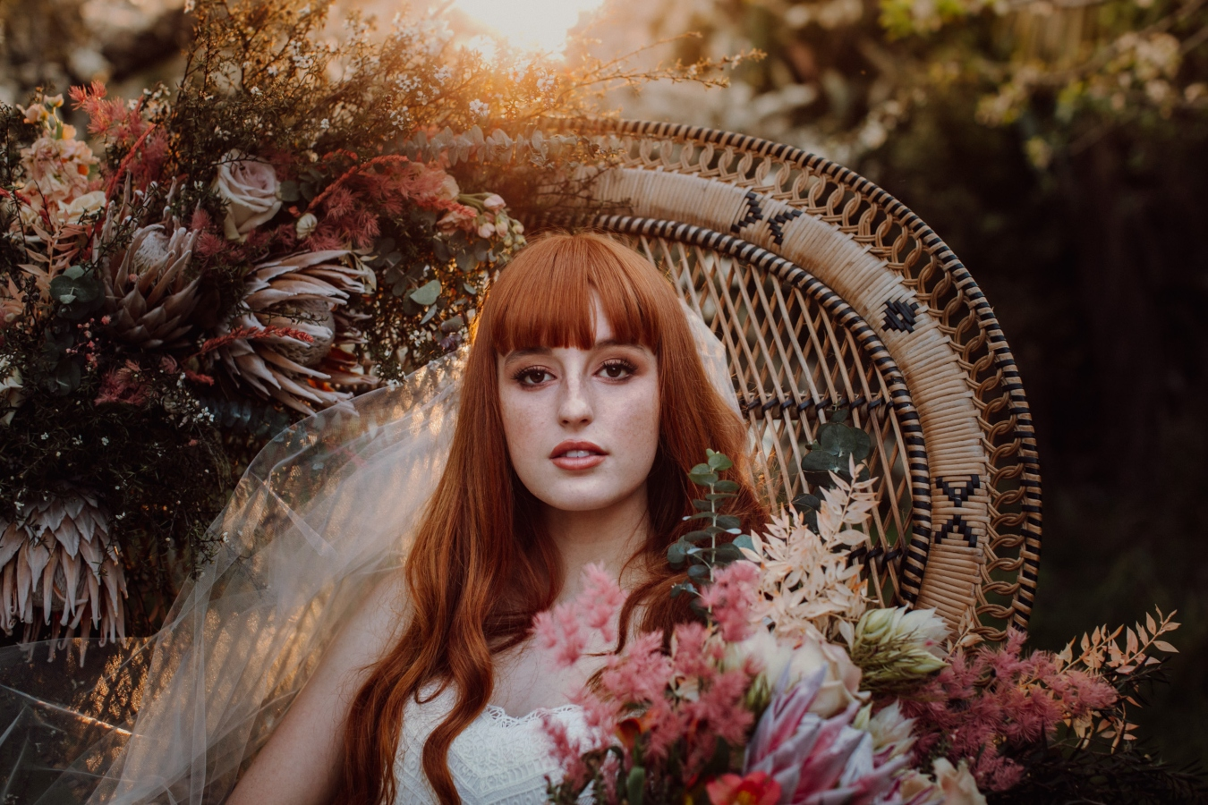Close up of Bride sitting in cane chair in orchard, leaning to her left and holding bouquet of flowers on arm of chair