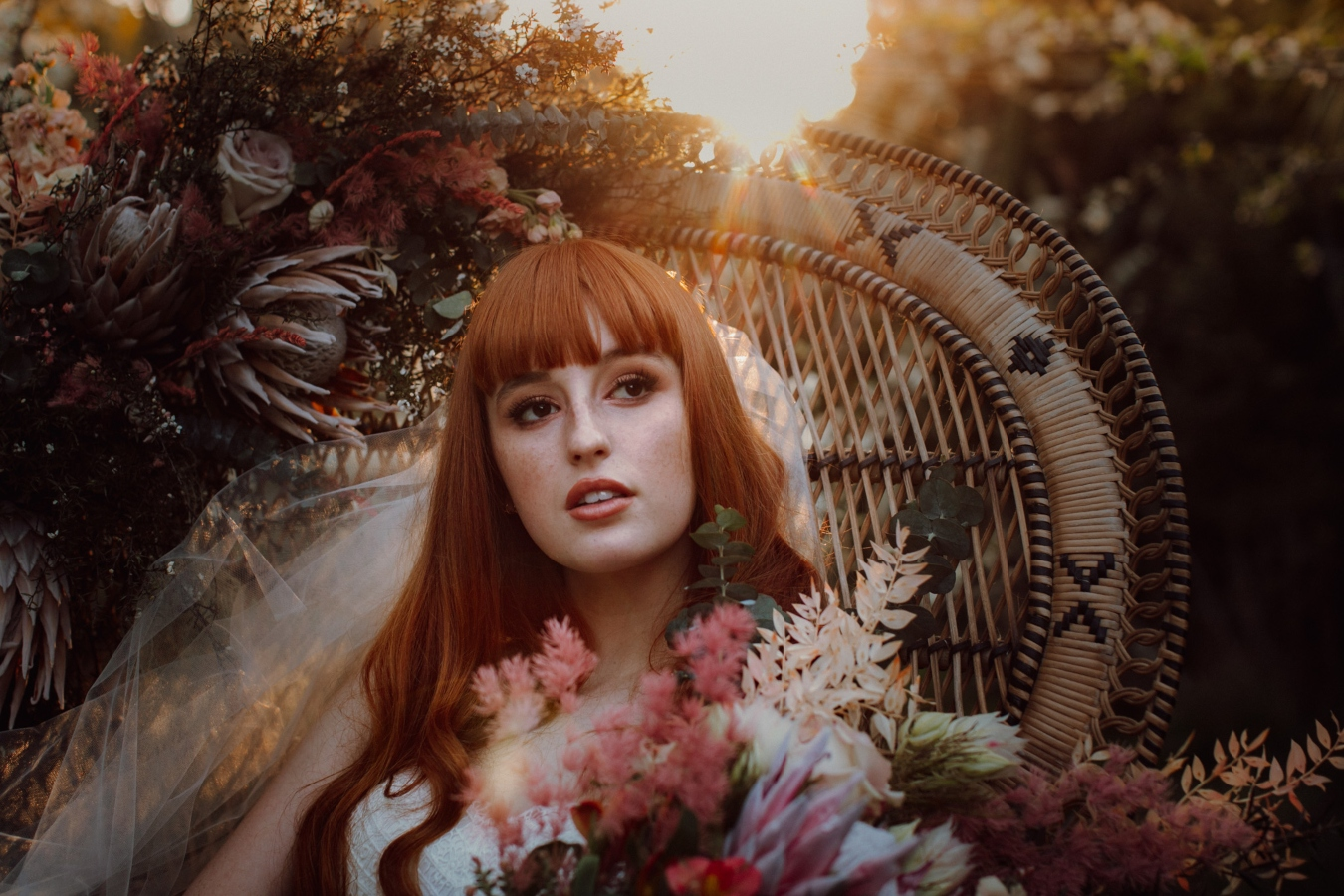 Close up of Bride sitting in cane chair in orchard, leaning to her left and holding bouquet of flowers on arm of chair and sun through the trees