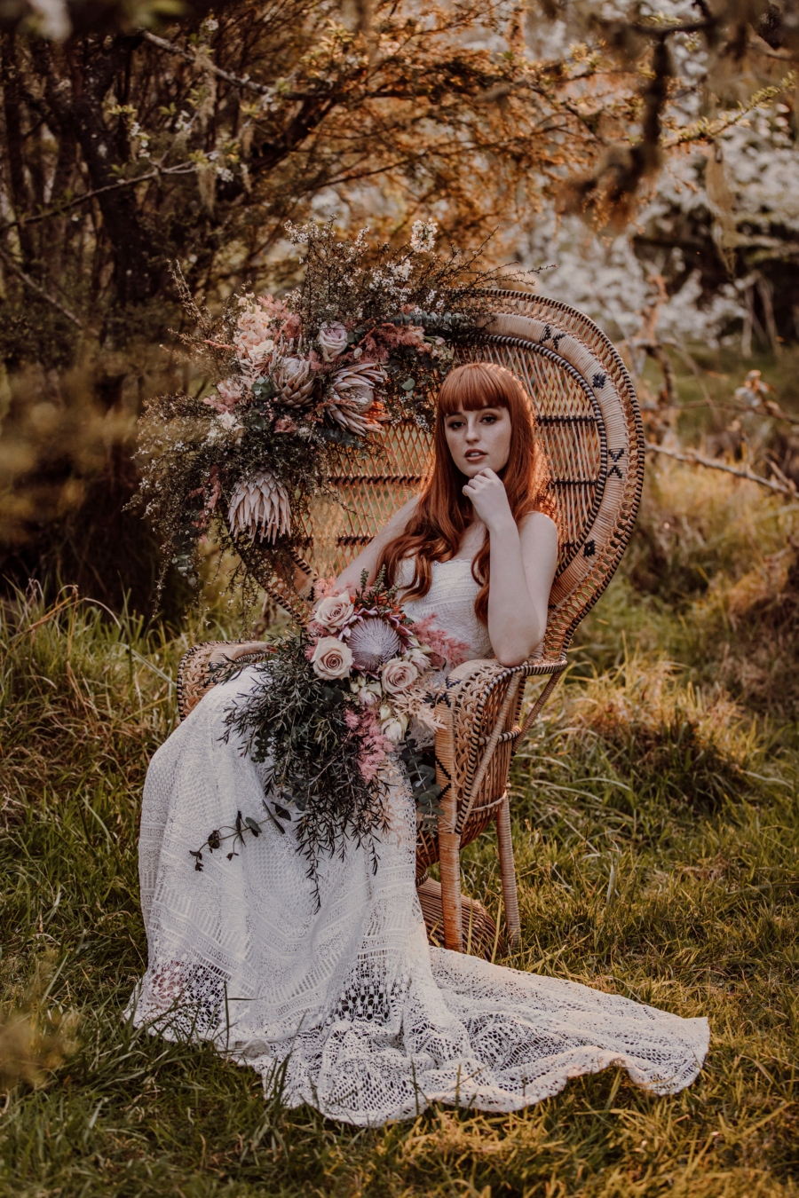 Bride in cane chair, resting chin on hand