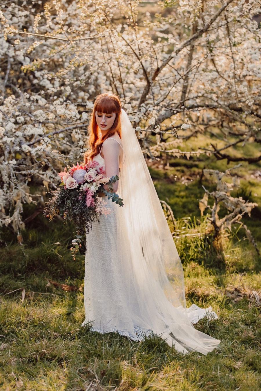 Bride standing below blossoming tree in orchard holding bouquet of flowers