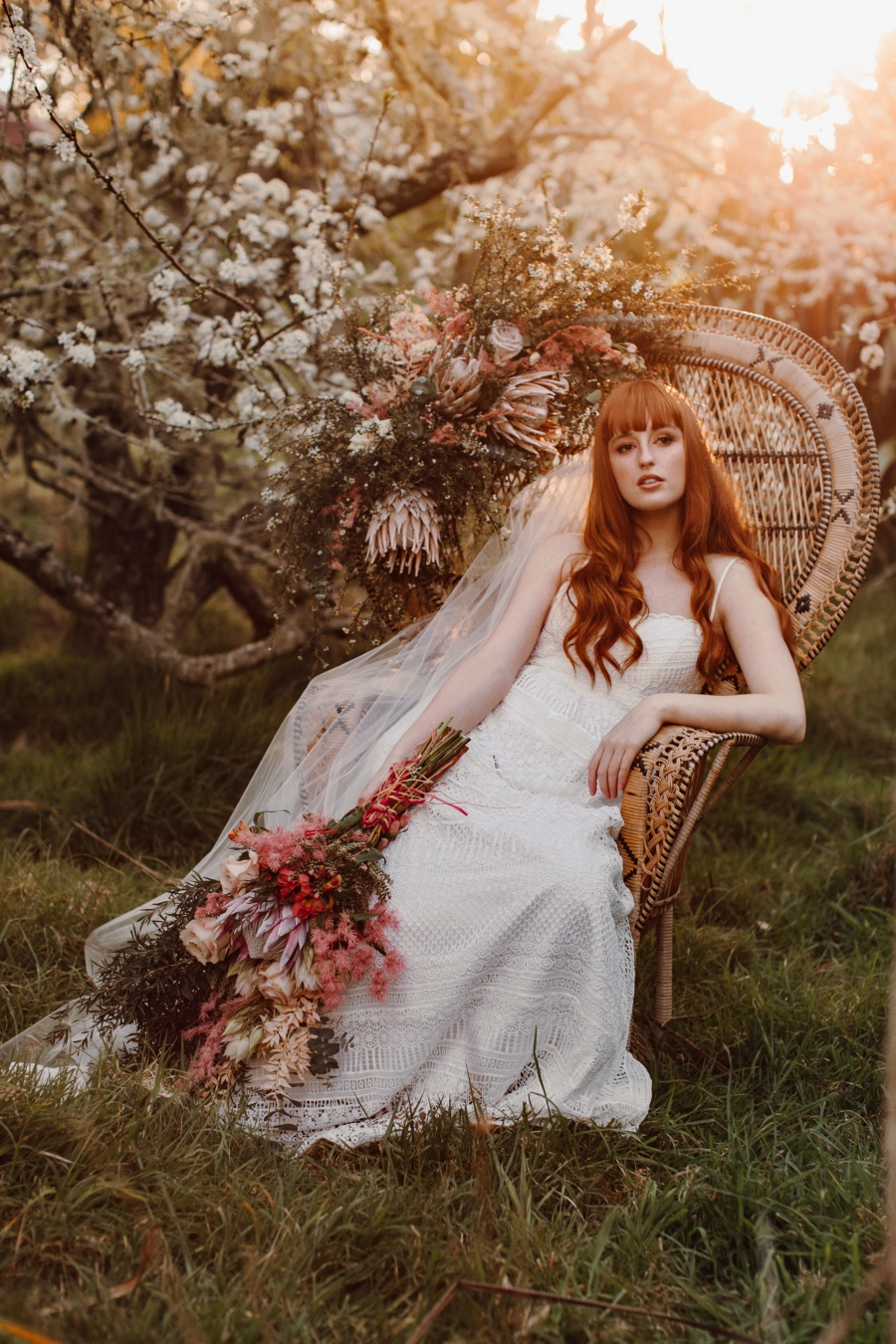 Bride sitting in cane chair in orchard, leaning to her left and holding bouquet of flowers down against her leg