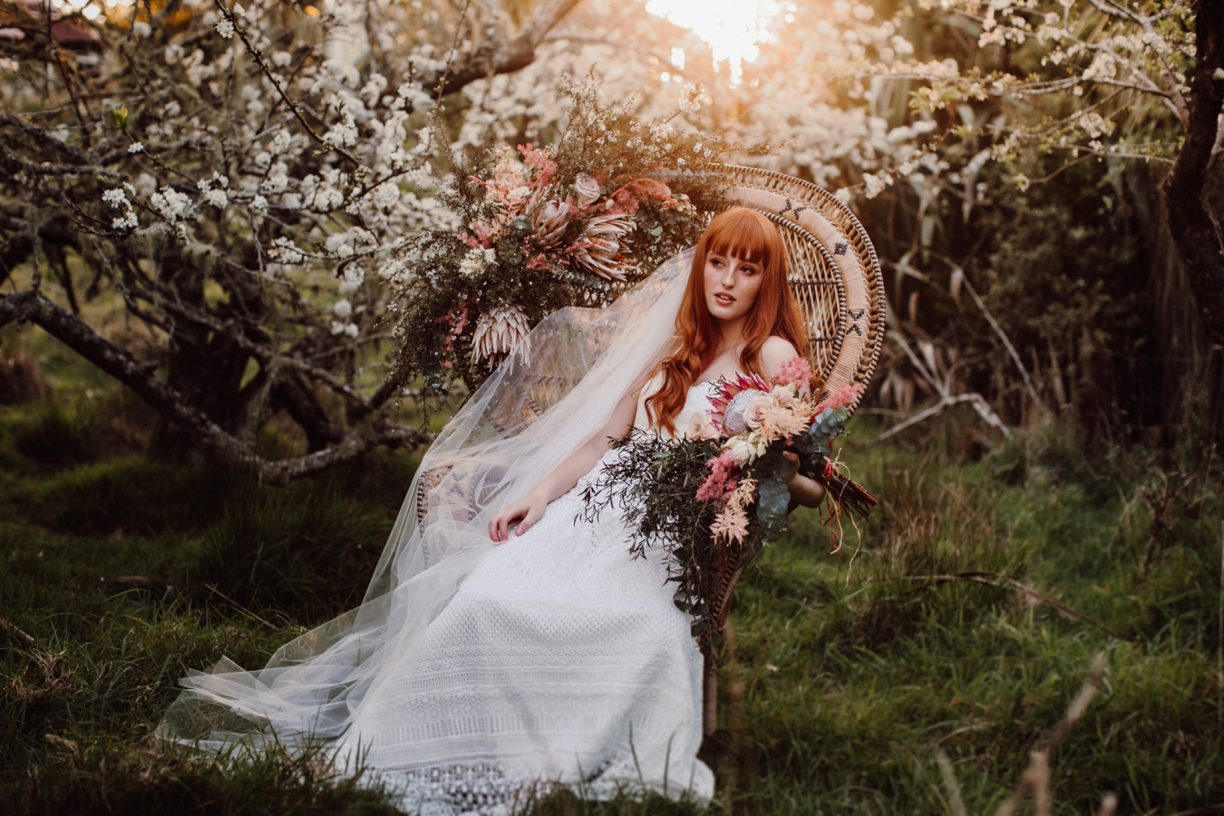 Bride sitting in cane chair in orchard, leaning to her left and holding bouquet of flowers on arm of chair